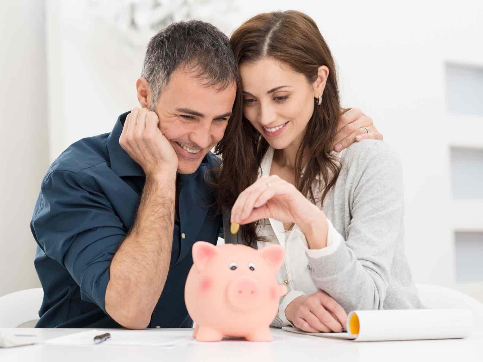 Casal coloca moeda em mealheiro